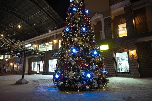 Tir extérieur d'arbre de noël dans les lumières sur la rue la nuit