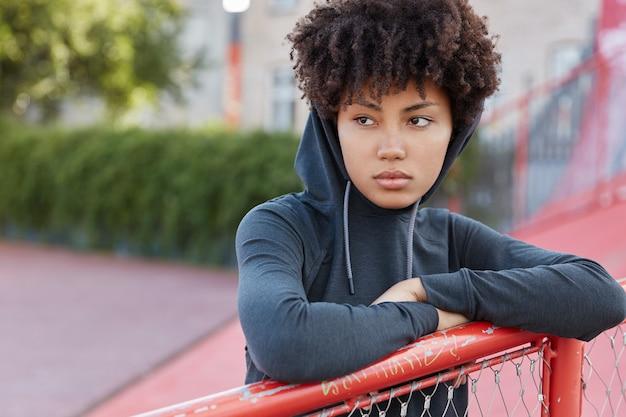 Tir extérieur d'un basketteur réfléchi en sweat à capuche élégant, pose sur le court, regarde pensivement de côté