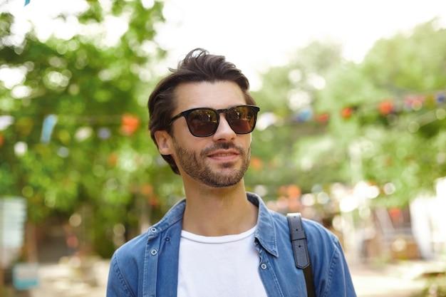 Tir extérieur du beau jeune homme barbu à lunettes de soleil posant sur le jardin de la ville par une chaude journée ensoleillée, vêtu d'une chemise bleue et d'un t-shirt blanc