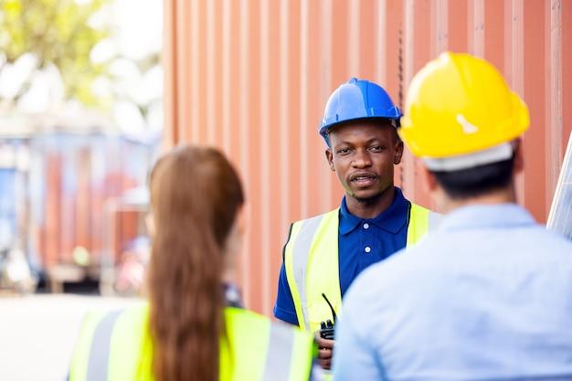 Tir extérieur d'un ingénieur africain noir inspecter un panneau solaire électrique portant un casque, des lunettes de protection et un équipement de sécurité,