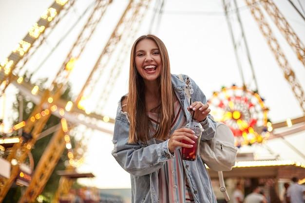 Tir extérieur de joyeuse jeune femme aux cheveux longs en robe romantique et manteau de jeans posant sur la grande roue, gardant une tasse de limonade dans les mains et souriant joyeusement