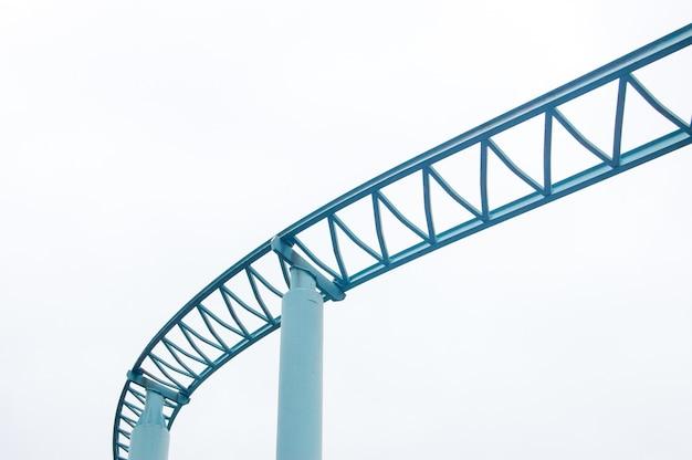 Tir à faible angle de rails de montagnes russes isolé sur fond de ciel blanc