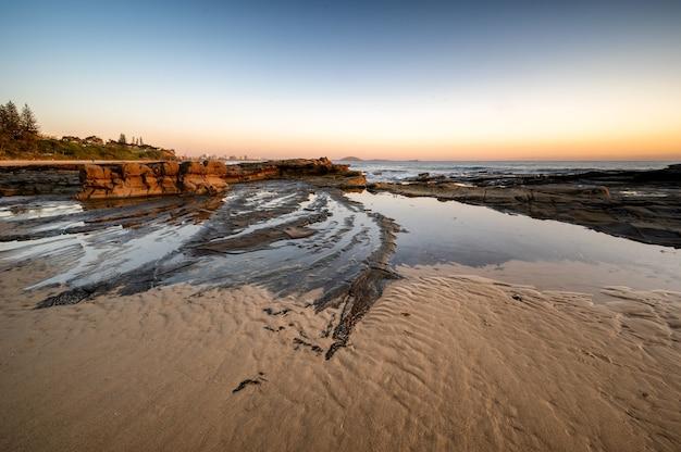 Tir fascinant d'une plage de sable au coucher du soleil