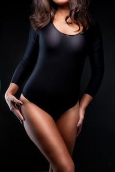 Tir d'une femme sexy en lingerie noire sur fond noir