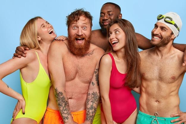 Tir horizontal d'amis heureux posant sur la plage