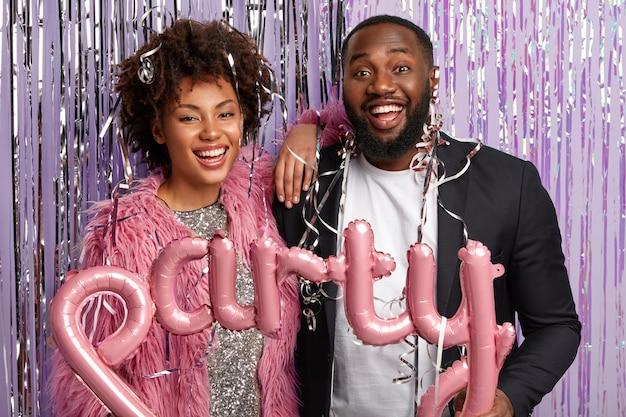 Tir horizontal du couple optimiste posent avec des guirlandes et des ballons