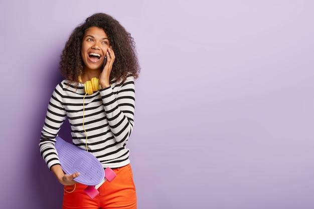 Tir horizontal d'une femme optimiste insouciante aux cheveux noirs bouclés, appelle le meilleur ami, a la bonne humeur