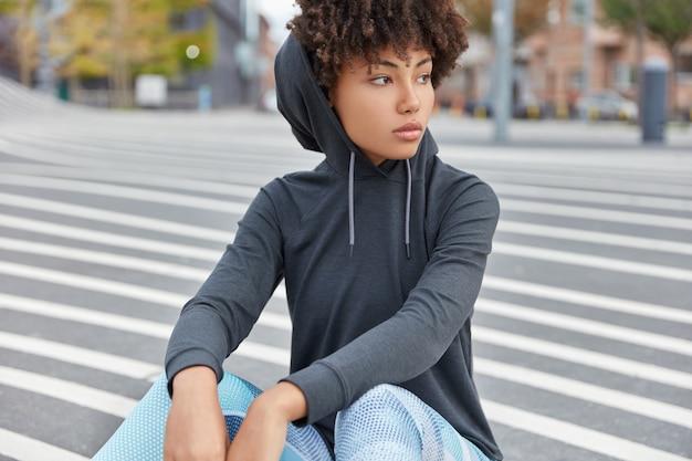 Tir horizontal d'une fille africaine swag réfléchie avec une expression pensive