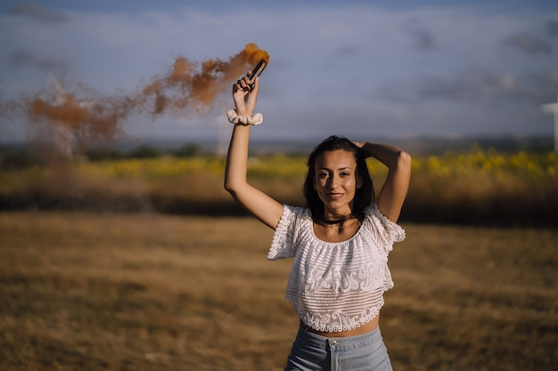 Tir horizontal d'une jeune femme de race blanche posant avec une bombe fumigène dans un champ