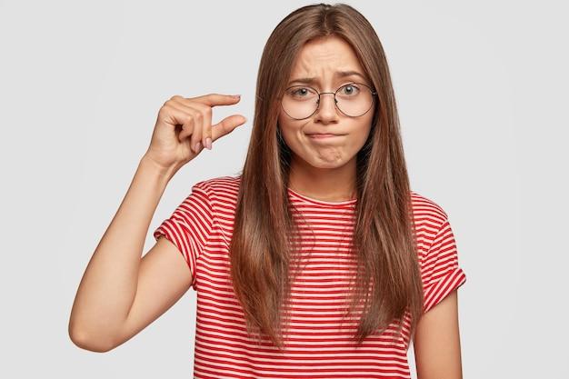 Tir horizontal de jeunes a le mécontentement de l'expression du visage façonne un objet minuscule avec les doigts, appuie sur les lèvres de mécontentement,