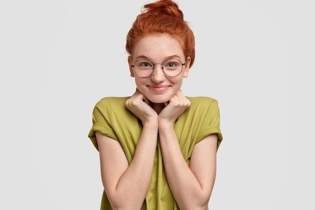 Tir horizontal de jolie femme tête rouge garde les deux mains sous le menton, se sent heureux comme reçoit des félicitations, vêtu de vêtements décontractés, lunettes rondes, isolé sur un mur blanc