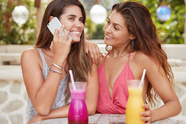 Tir horizontal de jolies jeunes femmes lesbiennes récréatives au café confortable en plein air