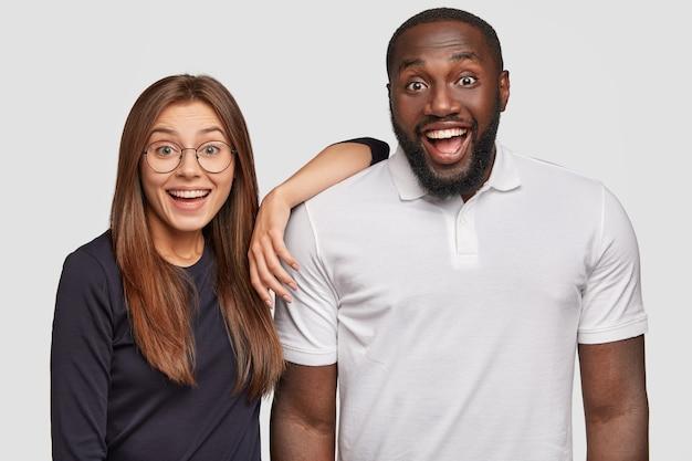 Tir horizontal de joyeux couple métis satisfait regarde avec des expressions heureuses étonné