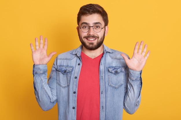 Tir horizontal de joyeux joyeux drôle ayant barbe, levant les bras, faisant le geste,