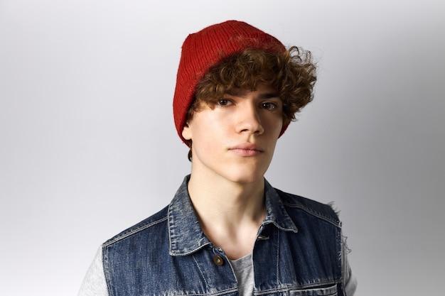 Tir horizontal d'un mec à la mode cool sérieux avec des cheveux bouclés et des yeux bruns étant confiant portant des jeans élégants et un chapeau d'hiver rouge posant isolé