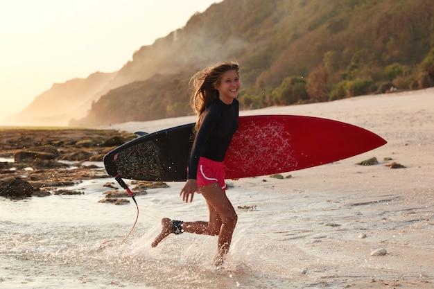 Tir horizontal de surfeur expérimenté gai s'exécute sur l'eau, exprime des émotions positives