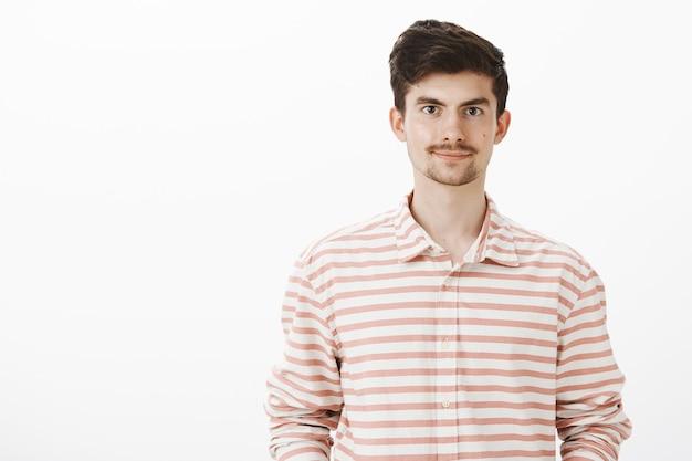 Tir intérieur de beau petit ami caucasien agréable en chemise rayée, souriant sympathique