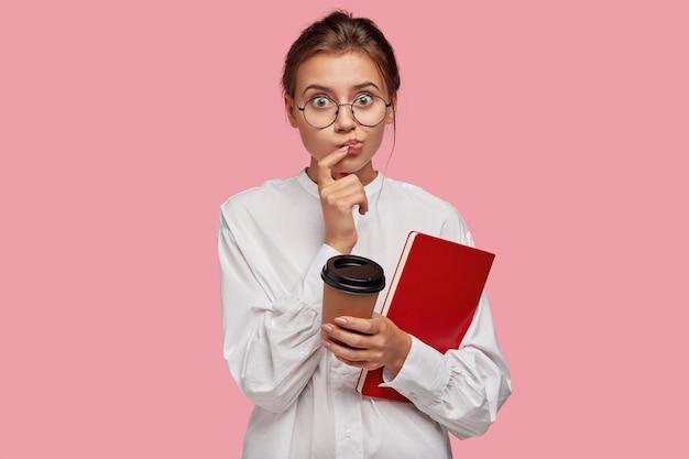 Tir intérieur de belle jeune femme avec des lunettes posant contre le mur rose