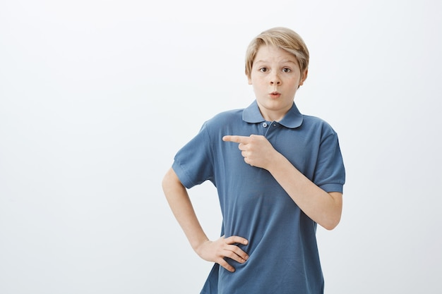 Tir intérieur de charmant garçon blond étonné nerveux en t-shirt bleu, tenant la main sur la hanche et pointant vers la gauche avec l'index