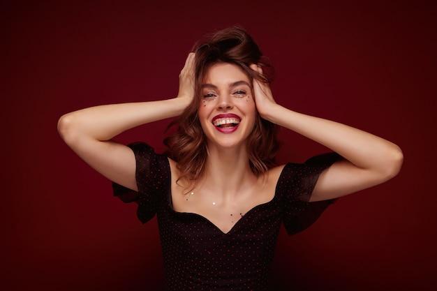 Tir intérieur de la charmante jeune femme brune en haut noir élégant avec des points rouges serrant joyeusement sa tête et riant joyeusement tout en posant