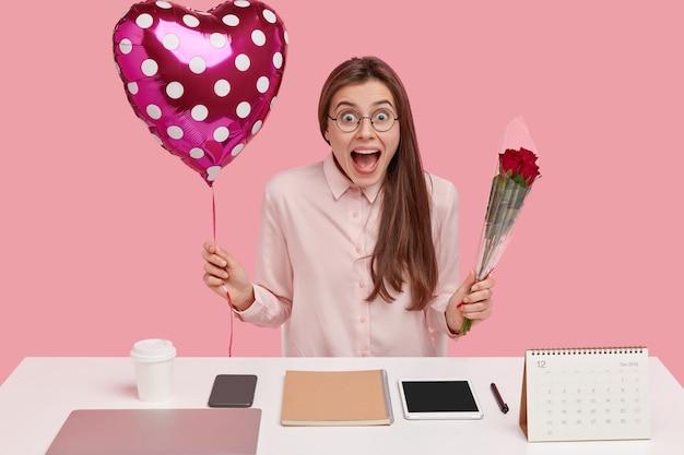 Tir intérieur d'une femme européenne joyeuse tient un ballon et des roses, a une expression positive, aime les relations au travail