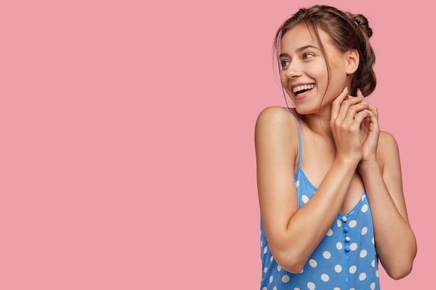 Tir intérieur d'une femme souriante heureuse garde les mains jointes