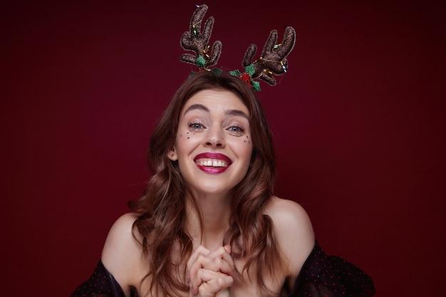Tir intérieur d'une jeune brune charmante et joyeuse avec une coiffure ondulée appréciant la mascarade de soirée à thème x-mas et souriant joyeusement, vêtue de vêtements élégants