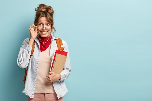 Tir intérieur d'un jeune étudiant heureux et beau porte des lunettes rondes optiques