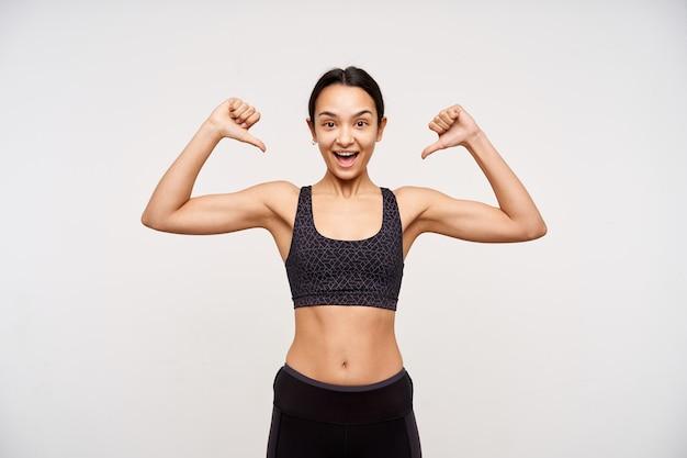 Tir intérieur d'une jeune femme aux cheveux bruns avec une coiffure décontractée, levant la main avec une bouteille d'eau et regardant à l'avant avec un visage mécontent, posant sur un mur blanc en tenue de sport