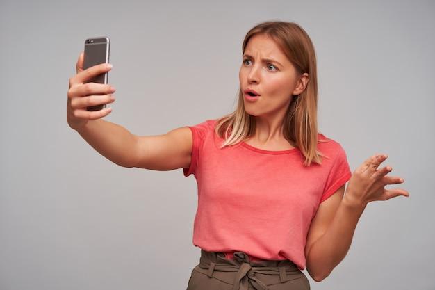 Tir à l'intérieur d'une jeune femme blonde confuse dans des vêtements décontractés portant du maquillage naturel tout en ayant une conversation téléphonique, debout sur fond blanc avec smartphone en main levée