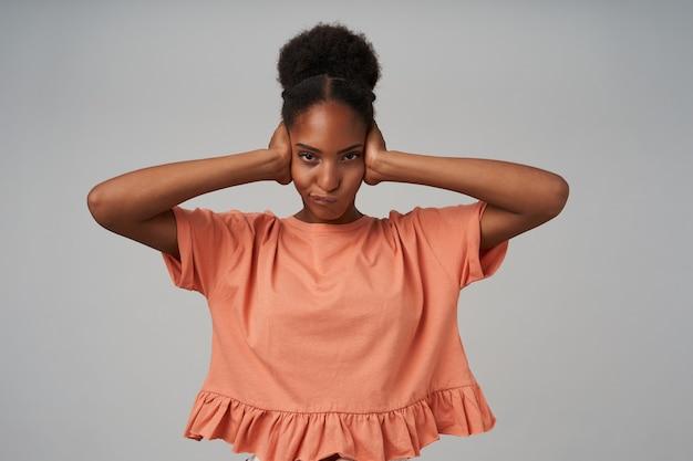 Tir intérieur de jeune femme bouclée aux cheveux bruns avec la fermeture des yeux avec les mains levées et regardant à l'avant avec la moue, posant sur un mur gris
