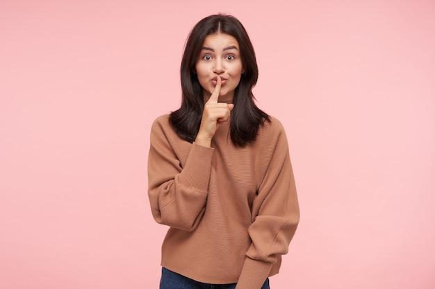 Tir intérieur de jeune femme brune aux cheveux longs agité, levant la main avec un geste silencieux tout en demandant de garder le silence, isolé sur un mur rose en tenue décontractée