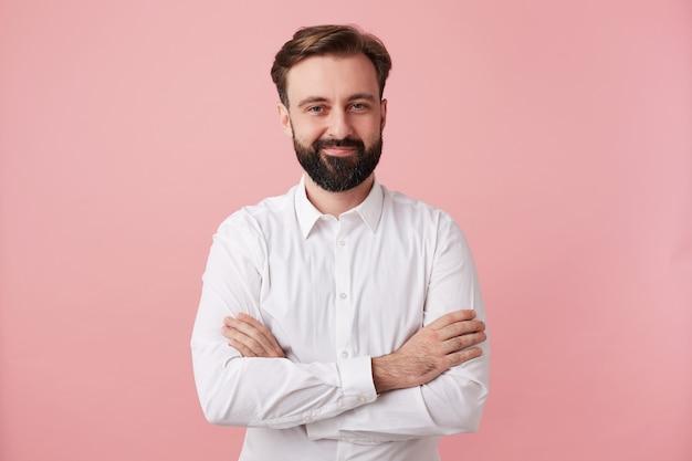 Tir à l'intérieur d'un jeune homme brune barbu à la recherche agréable avec une coiffure à la mode traversant la main sur sa poitrine en se tenant debout sur un mur rose, vêtu d'une chemise blanche