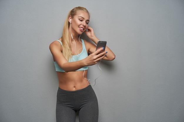 Tir intérieur de jolie jeune femme blonde mince faisant selfie avec smartphone tout en écoutant de la musique dans ses écouteurs, debout sur fond gris avec une coiffure en queue de cheval