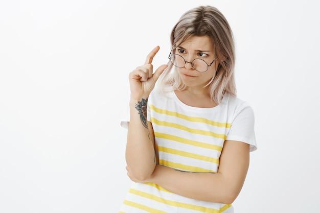 Tir intérieur de jolie jeune fille blonde avec des lunettes posant dans le studio