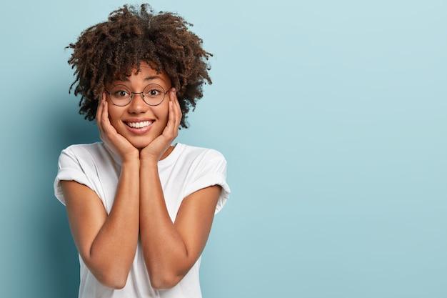 Tir isolé d'une belle femme afro positive à la recherche de deux mains sur le visage, sourit joyeusement, se réjouit de passer un bon week-end avec son petit ami, isolé sur un mur bleu, un espace vide pour votre publicité