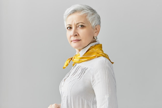 Tir isolé de jolie femme de 60 ans d'âge moyen confiant avec de courts cheveux gris va avoir à pied, portant un chemisier et un foulard en soie, posant contre un mur de fond blanc