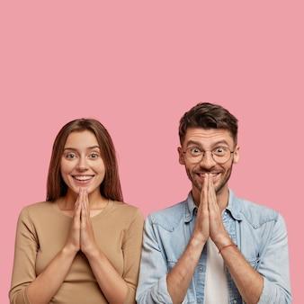 Tir isolé de joyeux jeune couple posant contre le mur rose