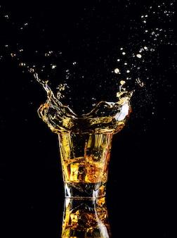 Tir isolé de whisky avec splash sur fond noir, brandy dans un verre