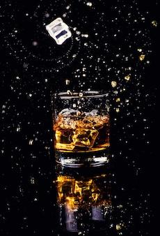 Tir isolé de whisky avec splash sur fond noir