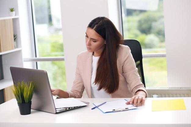 Tir d'une jolie jeune femme d'affaires travaillant sur un ordinateur portable sur son lieu de travail