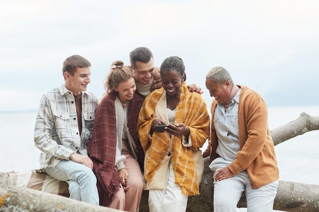 Tir minimal d'un groupe diversifié de jeunes sur la plage en automne ensemble à l'aide de l'espace de copie de smartphone