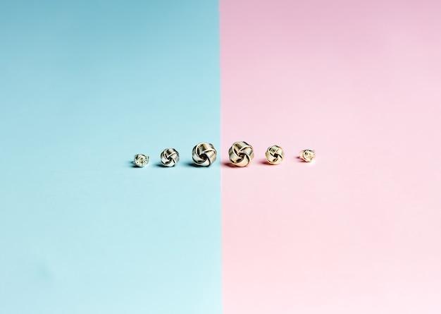 Tir minimaliste d'un groupe de boucles d'oreilles sur un fond rose et bleu pastel