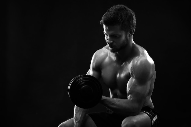 Tir monochrome d'un jeune sportif déchiré athlétique avec dumbb