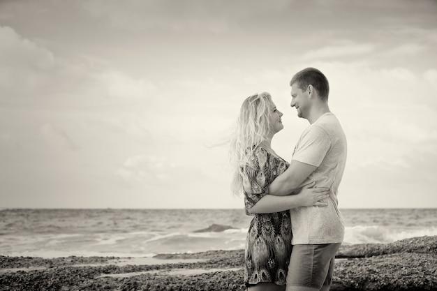 Tir monotone d'un couple heureux amoureux sur la plage, style vintage, avec une vignette