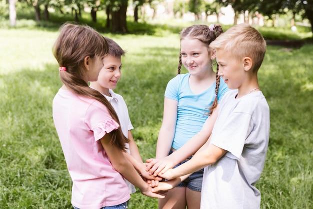 Tir moyen, enfants, tenant mains, ensemble