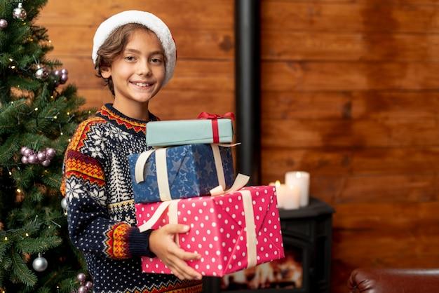 Tir moyen garçon avec des cadeaux près de sapin de noël
