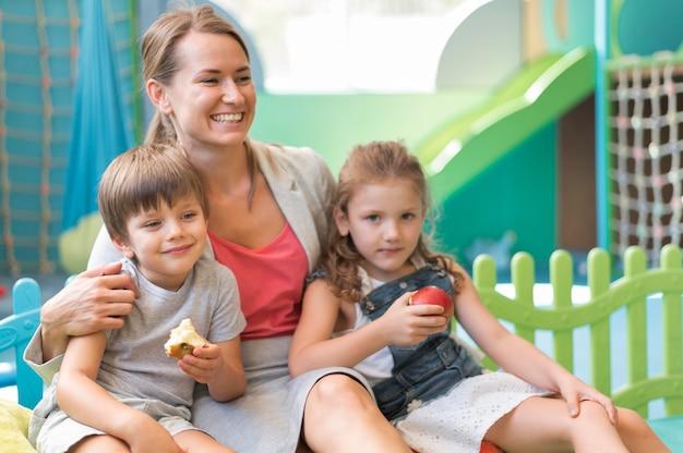 Tir moyen heureux enseignant tenant des enfants