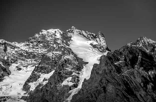 Tir en niveaux de gris de montagnes dont certaines parties sont couvertes de neige