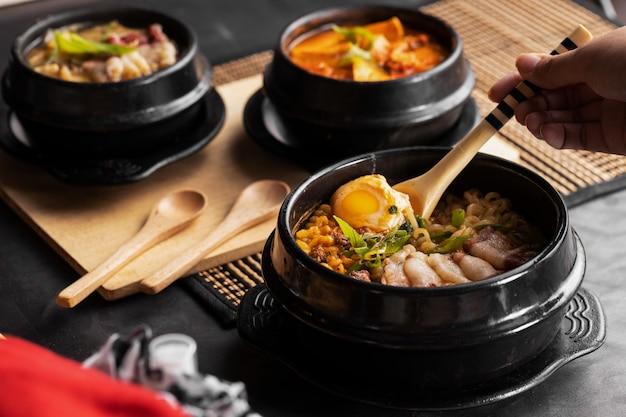 Tir d'une personne mangeant de la nourriture chinoise avec une cuillère d'une plaque noire